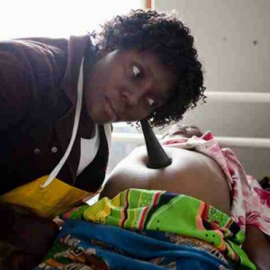 Malawian midwife using a foetal pinnard to listen to a baby's heartbeat in the womb